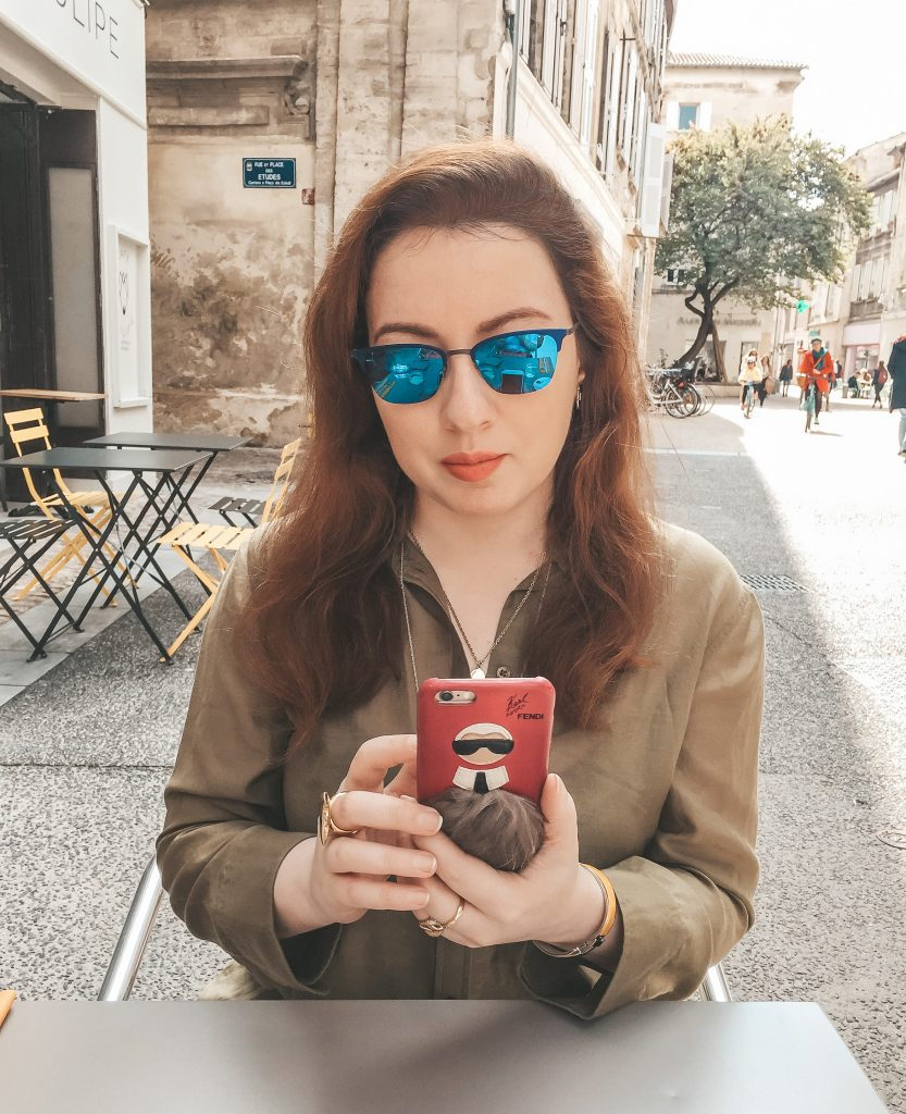 NYC fashion blogger sitting and holding Fendi Karlito iPhone case