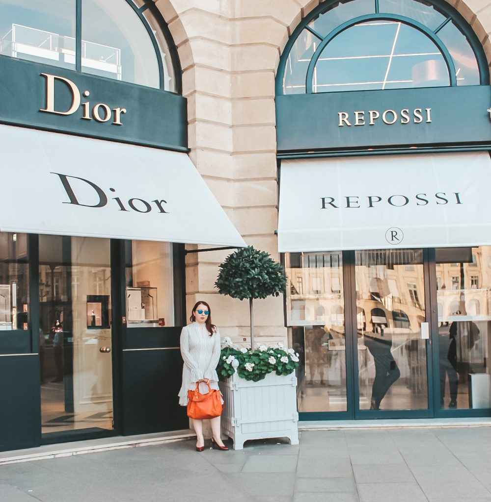 NYC fashion blogger outside Dior and Repossi boutique in Paris wearing Derek Lam white striped dress, Balenciaga red city bag, Modo blue sunglasses