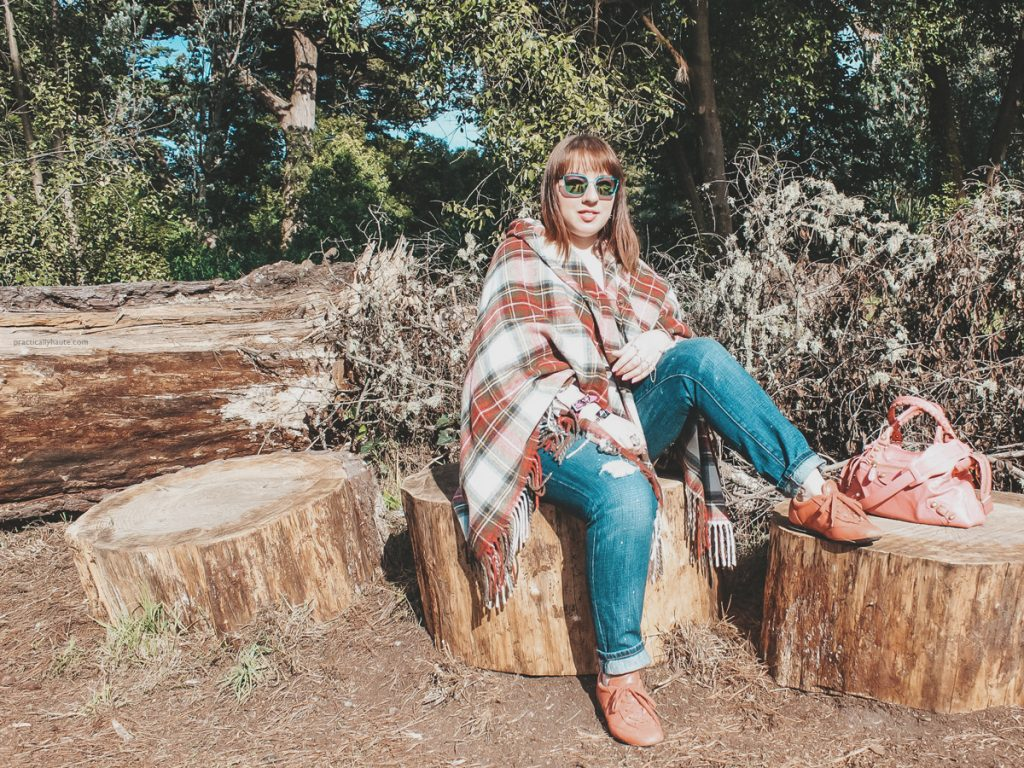 Fashion blogger sitting on a tree stump in a park. Wearing plaid tartan cape by Vivienne Westwood, blue jeans, Hogan pink sneakers, and pink Balenciaga bag.