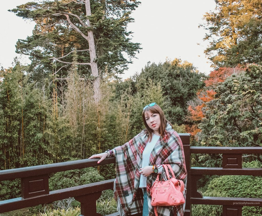 NYC fashion blogger wearing Vivienne Westwood Anglomania plaid tartan cape. Overlooking a park landscape with green, yellow, and red leaves trees.